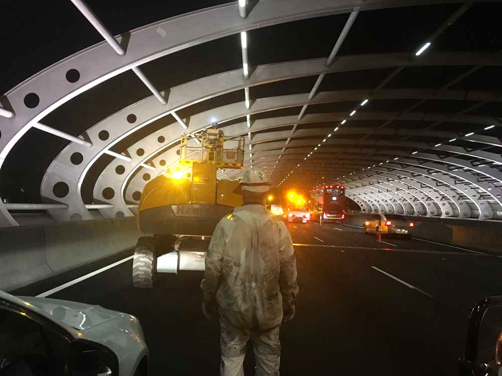 Night construction workers on freeway overpass