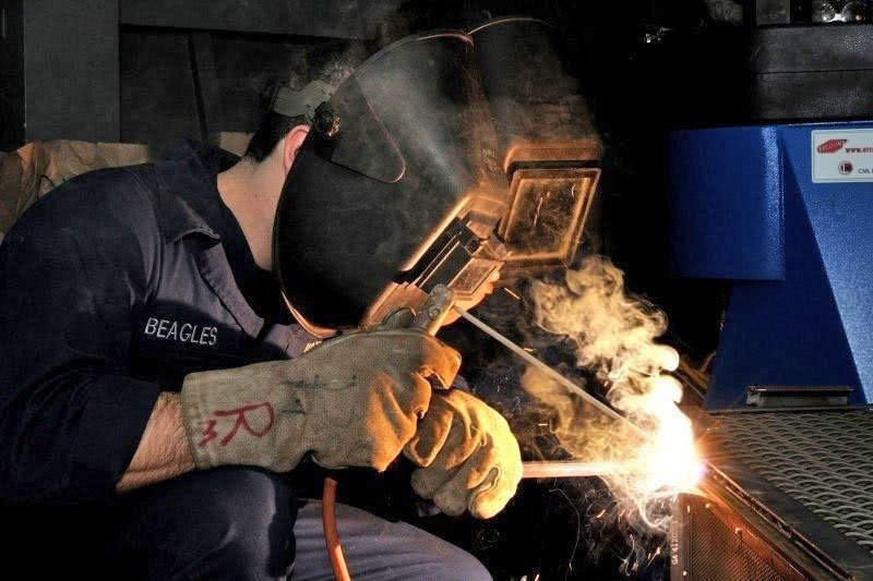 welder welding metal in safety mask and gloves